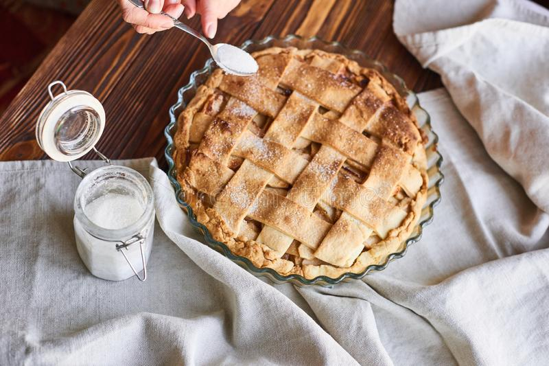 Cooking baking concept. Making rustic American style apple pie, top view on table with sugar. Homemade apple pie on the brown wooden table. Apple tart with royalty free stock image