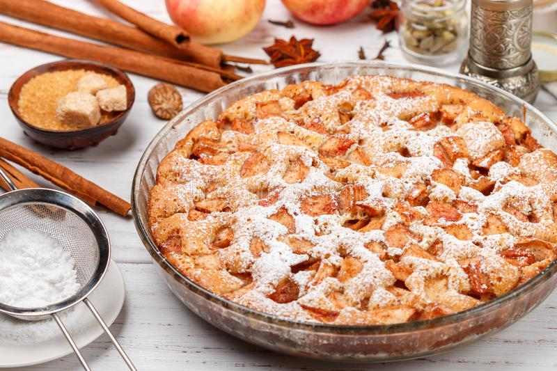 Homemade Apple pie with cinnamon, cardamom, anise and powdered sugar. Tasty treat in a rustic style. Selective focus stock photo