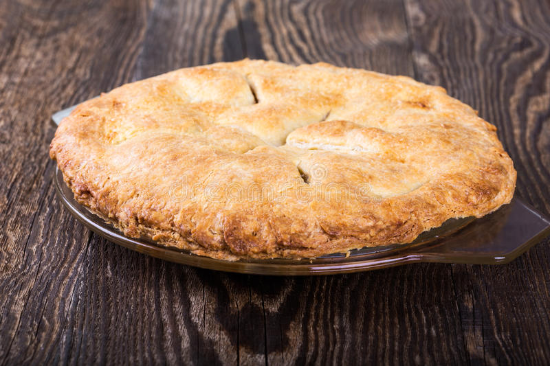 Homemade apple pie. With a flaky pie crust and sliced apples, sugar, allspice, cinnamon, vanilla on rustic wooden table stock photos