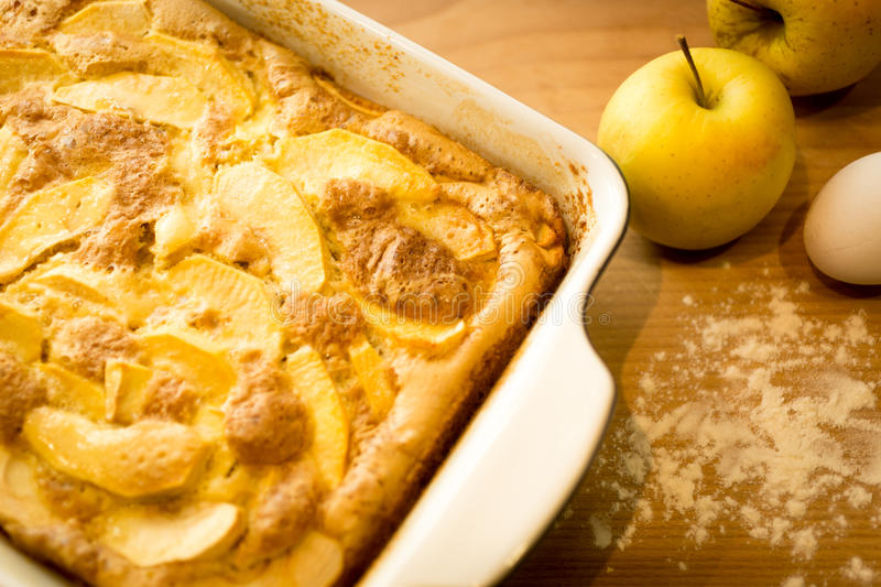Homemade apple pie with fresh apples on kitchen table. Homemade apple pie with fresh apples on wooden kitchen table stock photo