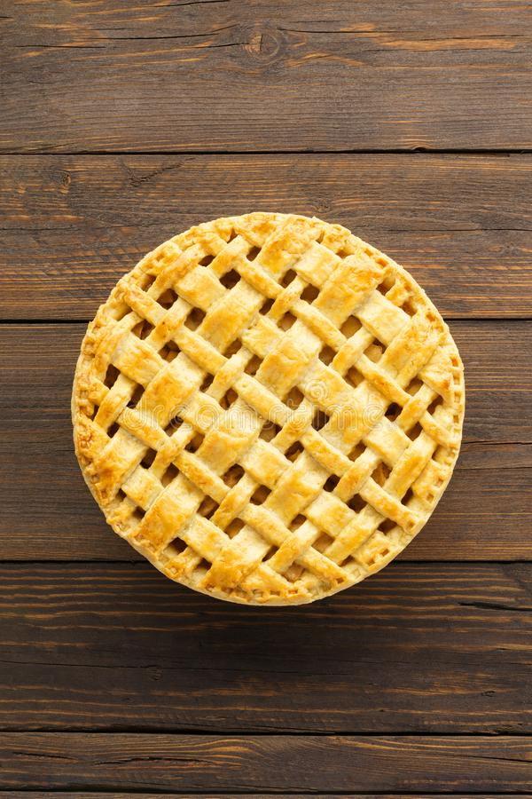 Homemade apple pie with lattice top on brown wooden background. Overhead shot. Space for text royalty free stock photo