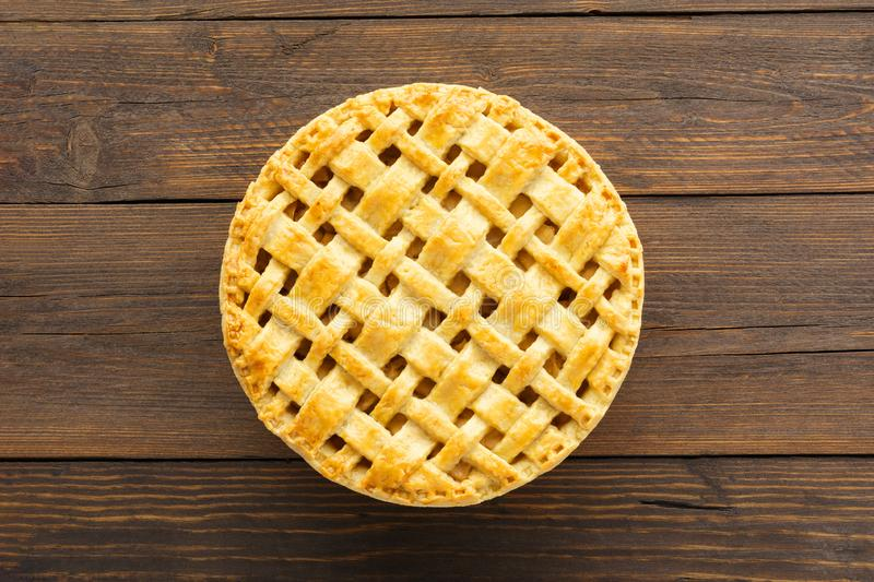 Homemade apple pie with lattice top on brown wooden background. Overhead shot. Space for text stock image