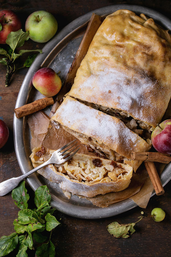Homemade apple strudel. Sliced homemade apple strudel served with fresh apples with leaves, cinnamon sticks and sugar powder on vintage metal tray with fork over stock photo
