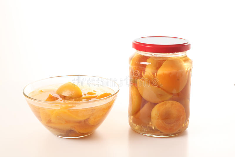 Homemade apricot compote. In a glass jar and in a glass bowl for presentation. Everythig is on a white background stock photography