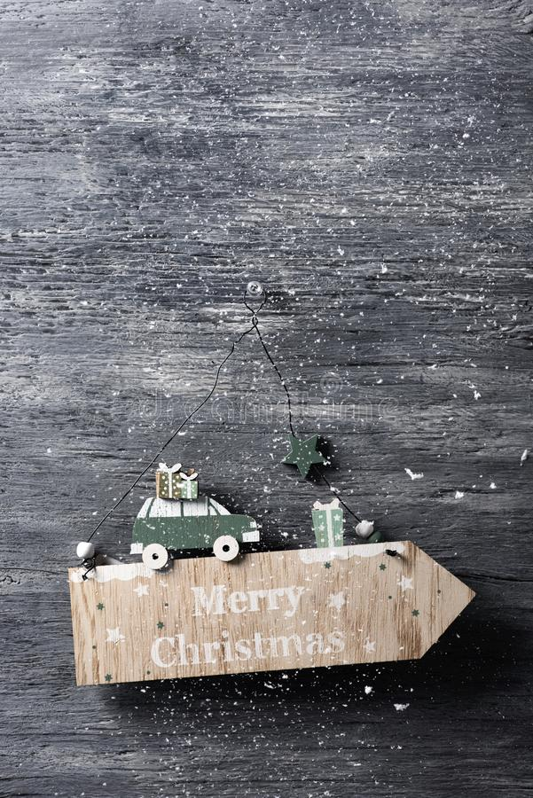 Text merry christmas in a wooden signboard. A homemade arrow-shaped wooden signboard with the text merry christmas written in, pinned in a gray rustic wooden royalty free stock images