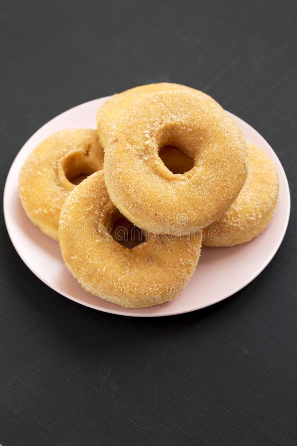 Homemade autumn apple-cinnamon donuts on a pink plate on a black surface, low angle view. Closeup.  stock photos