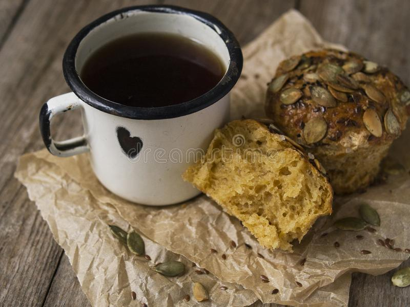 Homemade Autumn Pumpkin Muffins with cheese, paprika and sea salt ready to eat with a metal mug of tea on wooden background. Copy stock image