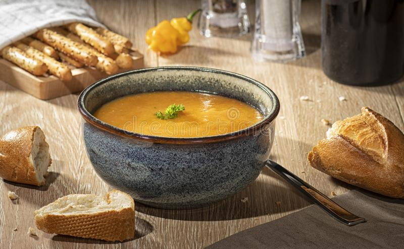 Pumpkin soup on a wooden table with bread. stock photography