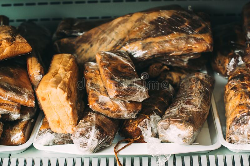 Homemade bacon and smoked lard in the street market. Traditional cured meat products for sale at outdoor farmers market. Vacuum- royalty free stock image