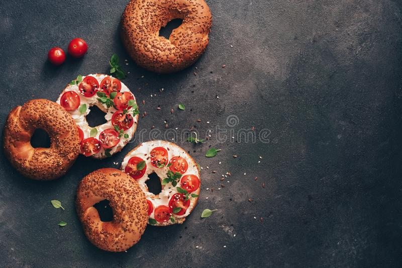Homemade bagel sandwich with cream cheese, cherry tomatoes and basil sprinkled with sesame and flax seeds, dark rustic background royalty free stock photography