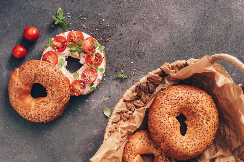 Homemade bagel sandwich with soft cheese, cherry tomatoes and basil sprinkled with sesame and flax seeds, dark rustic background. royalty free stock photos