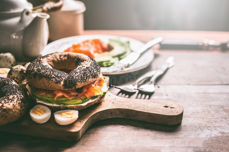 Homemade bagel sandwich topped with salmon, avocado , fresh cheese and cooked quail eggs on dark rustic wooden background. royalty free stock images