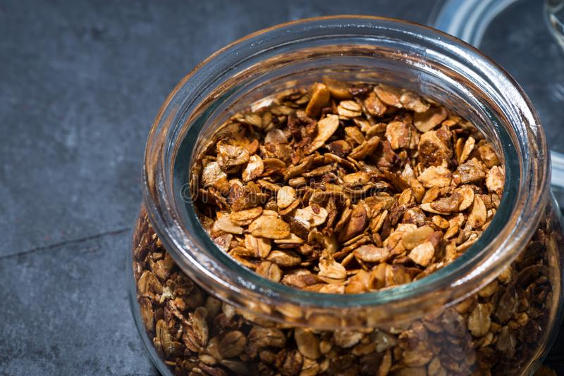 Homemade baked granola in a glass jar on dark background. Closeup, horizontal stock image