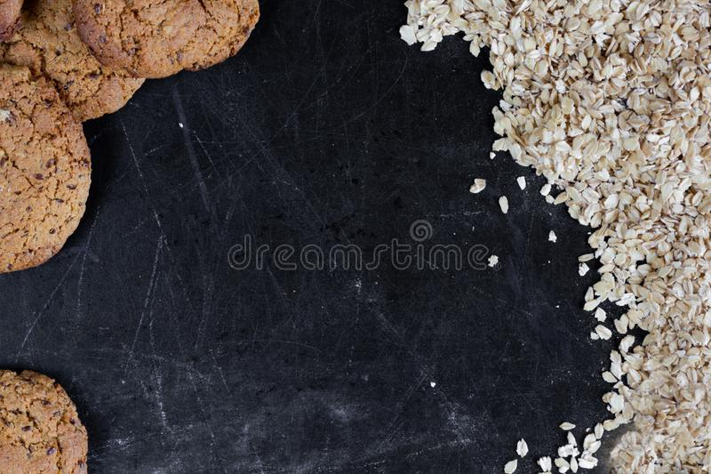 Homemade baked oatmeal cookies with linen seeds on balck background. Homemade baked oatmeal cookies with linen seeds on balck table stock image