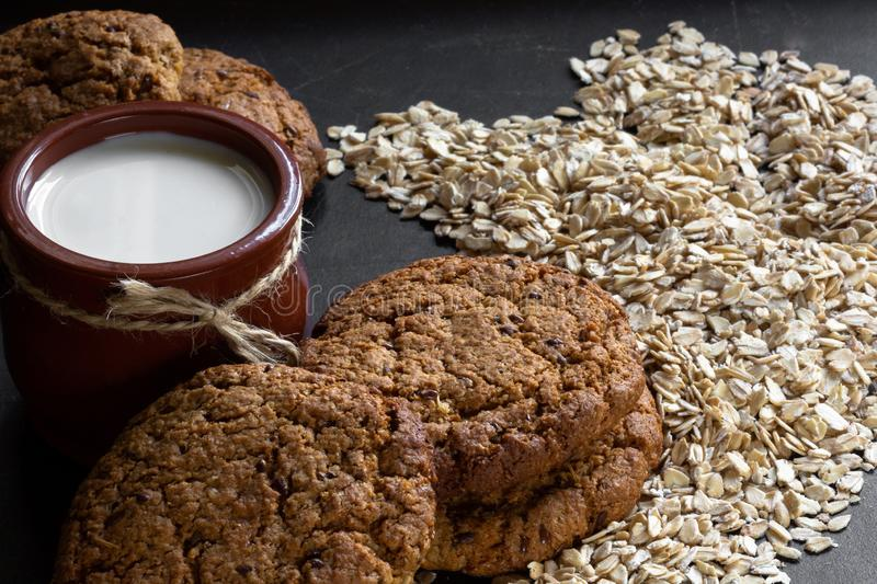 Homemade baked oatmeal cookies with linen seeds on balck background. Homemade baked oatmeal cookies with linen seeds on balck table stock photo