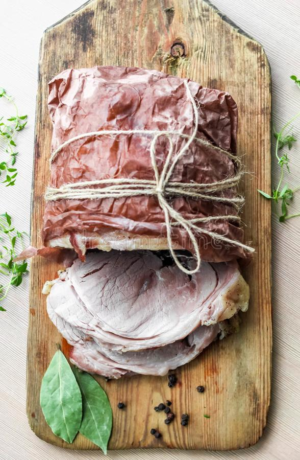Homemade baked pork ham with aromatic herbs. Festive traditional dish and Keto diet food. Homemade baked pork ham on rustic cutting board with aromatic herbs royalty free stock images