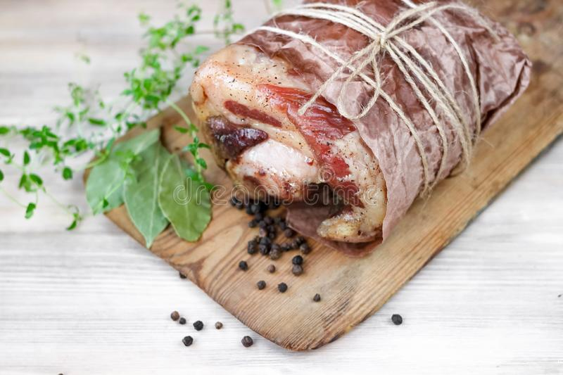 Homemade baked pork ham with aromatic herbs. Festive traditional dish and Keto diet food. Homemade baked pork ham on rustic cutting board with aromatic herbs royalty free stock photos