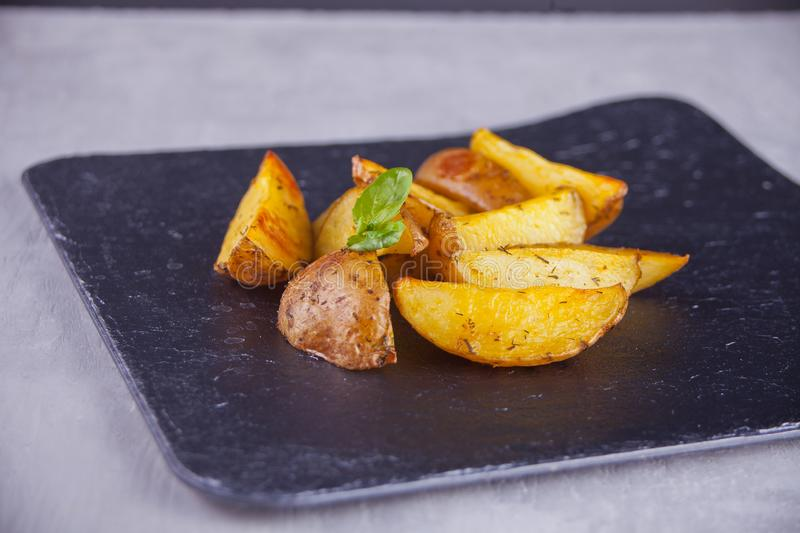 Homemade baked potato wedges with herbs on black background stock photo