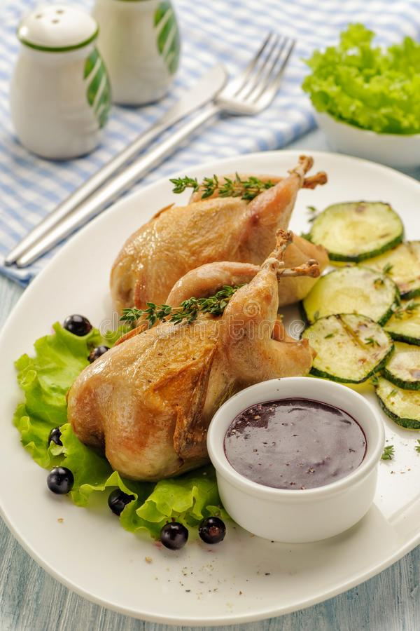 Homemade baked quails. With grilled zucchini and pepper garnish and berry sauce. On a white plate. Lunch and dinner for diet. Ketogenic diet. Vertical view stock photography