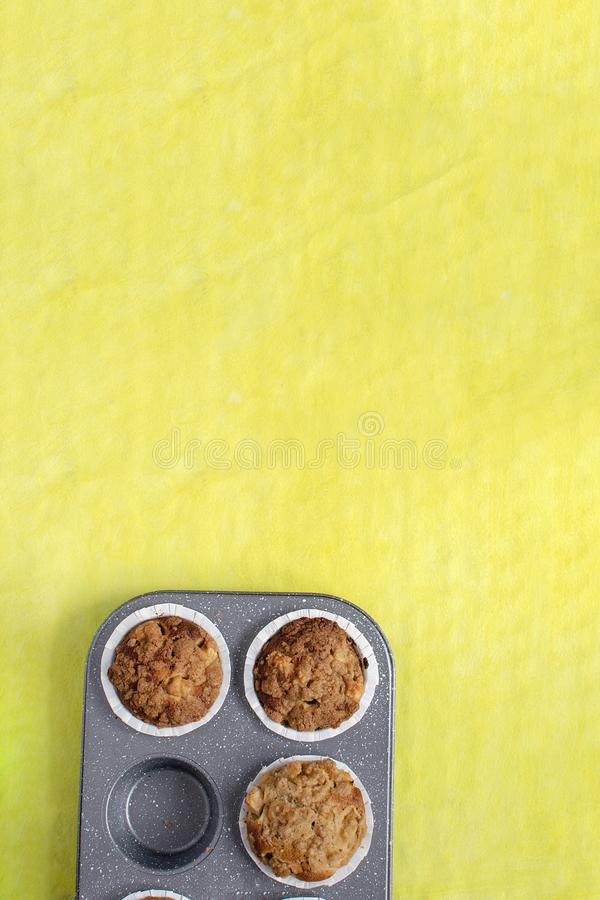 Homemade baking concept - fresh baked muffins on cooling rack, minimal picture, bright yellow background, top view, royalty free stock images