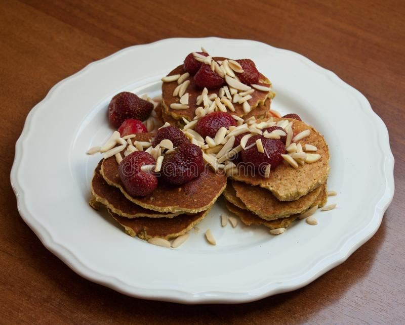 Homemade banana and oat pancakes with strawberries and almonds stock photos