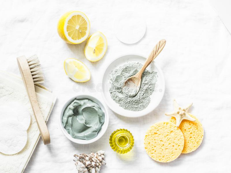 Homemade beauty facial mask. Clay, lemon, oil, facial brush - beauty products ingredients on light background. Top view royalty free stock photo