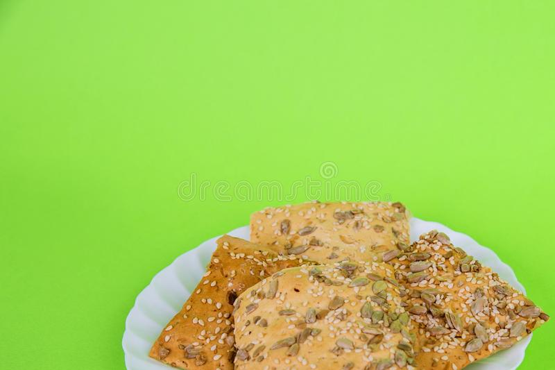 Homemade bee on a green background. crisp bread with sunflower, flax and sesame seeds. Dietary cookies stock photos