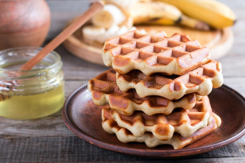 Homemade Belgian waffles with with bananas and honey on a plate stock image
