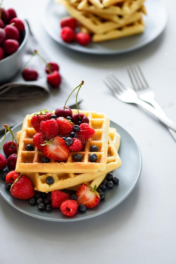 Homemade belgian waffles with berries on gray table. Healthy breakfast concept stock image