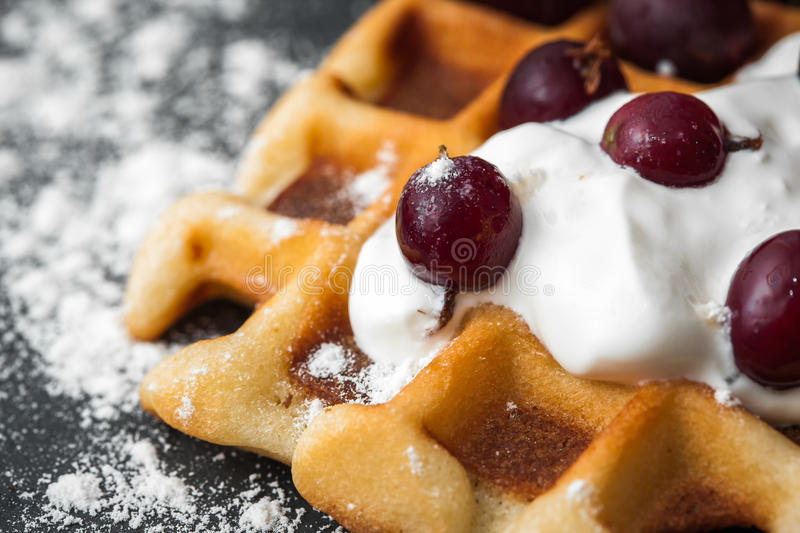 Homemade Belgian waffles with berries, whipped cream. Traditional homemade Belgian waffles with berries, whipped cream and powdered sugar on dark background stock image