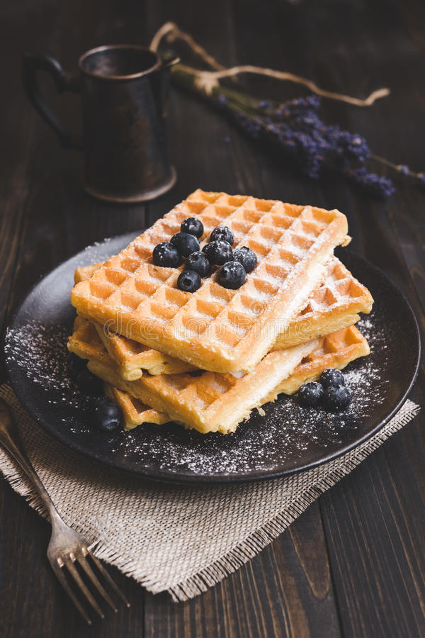 Homemade belgian waffles with blueberries on the dark wooden tab royalty free stock photography