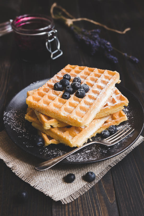 Homemade belgian waffles with blueberries on the dark wooden table stock photo
