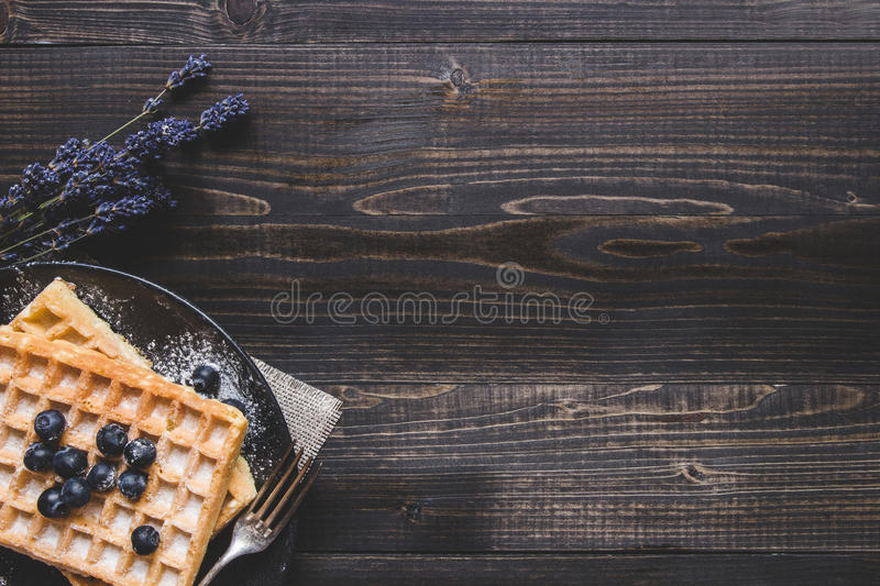 Homemade belgian waffles with blueberries on the dark wooden table with copy space stock photo