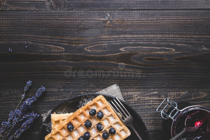 Homemade belgian waffles with blueberries on the dark wooden table with copy space royalty free stock photos