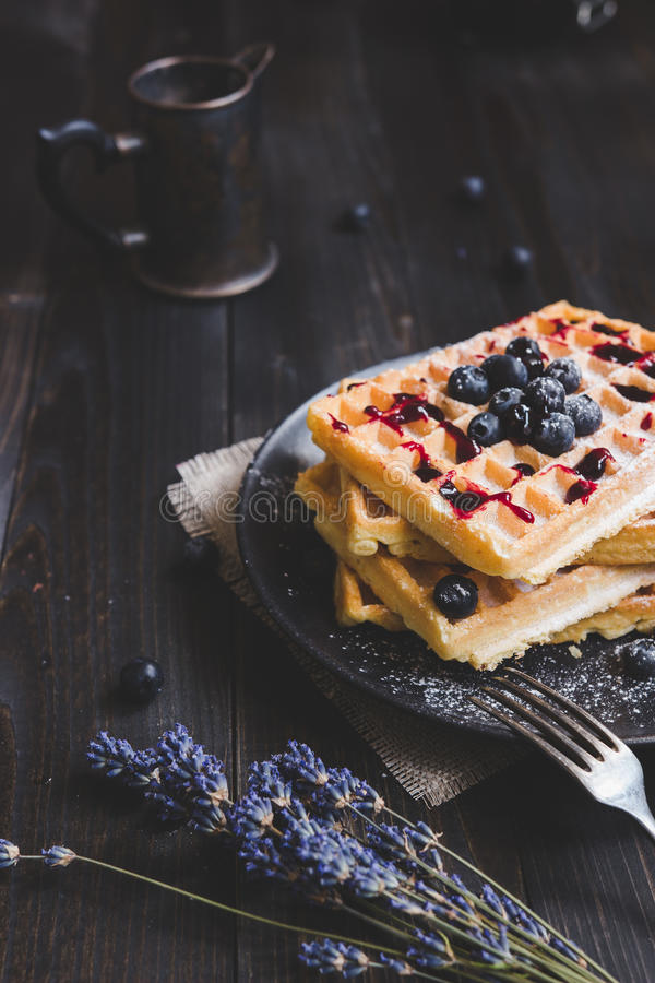 Homemade belgian waffles with blueberries and jam on the dark wooden table stock photo