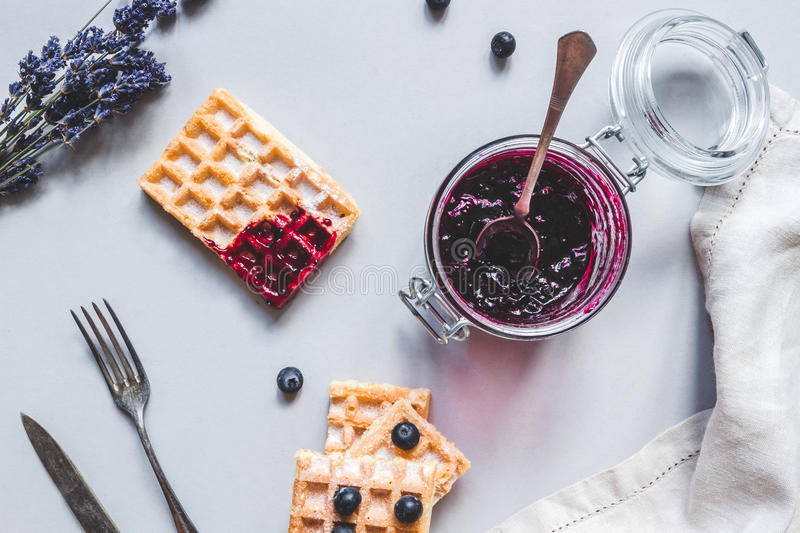Homemade belgian waffles with blueberries and jam on the light b royalty free stock photo