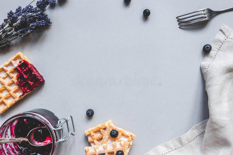 Homemade belgian waffles with blueberries and jam on the light blue table with copy space royalty free stock photography