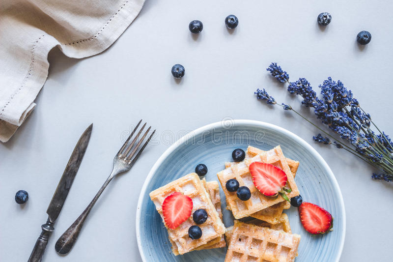 Homemade belgian waffles with blueberries and strawberries on the light blue table stock image