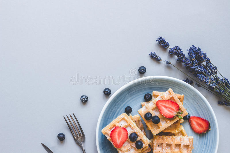 Homemade belgian waffles with blueberries and strawberries on th royalty free stock image