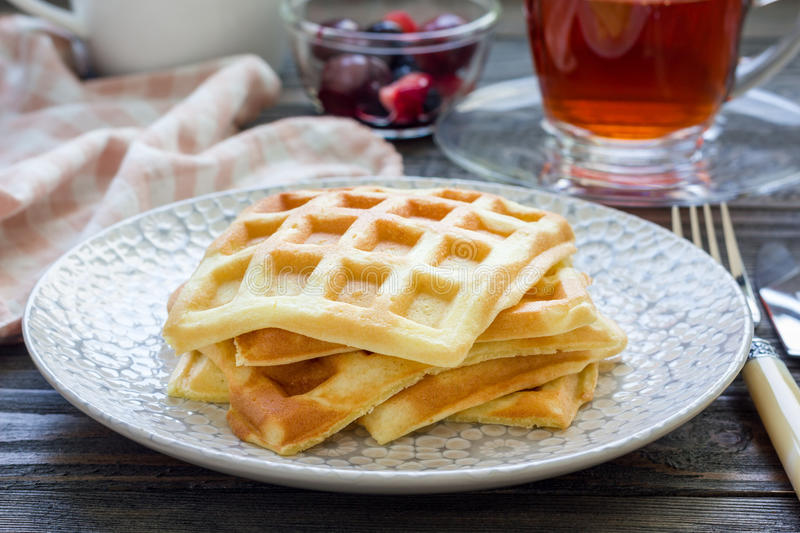Homemade belgian waffles for breakfast, served with fruit and tea royalty free stock photo
