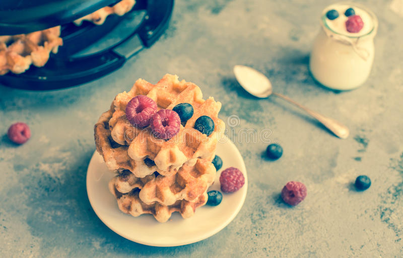 Homemade Belgian waffles with forest fruits, blueberries, raspberries and yogurt. stock photo