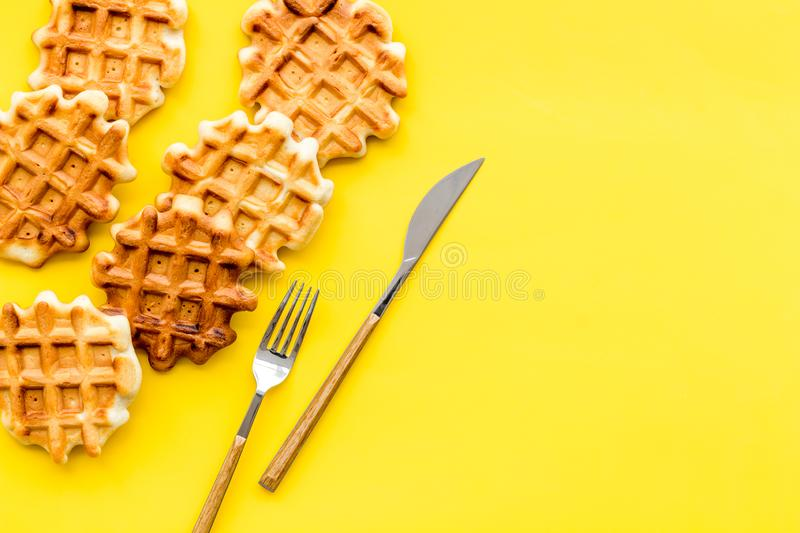 Homemade Belgian waffles on served table on yellow background top view copy space. Sweet snack. Viennese waffles. Homemade Belgian waffles on served table on royalty free stock photos