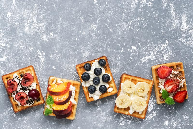 Homemade Belgian waffles with a variety of fruits on a gray background. Top view, copy space. stock photo
