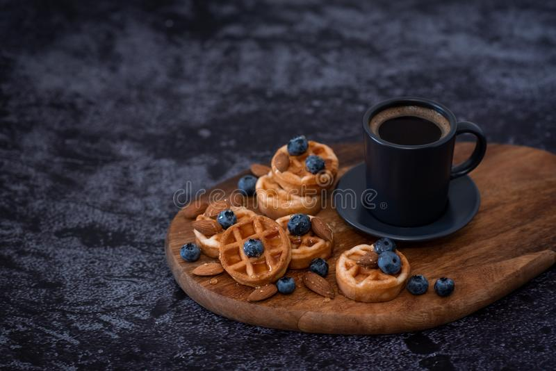 Homemade belgian waffles, white ceramic cup of coffee, milk, teaspoon and coffee beans. Dark rustic background. Space for text in royalty free stock photo