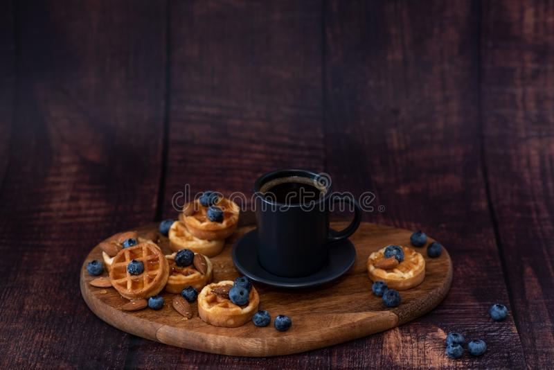 Homemade belgian waffles, white ceramic cup of coffee, milk, teaspoon and coffee beans. Dark rustic background. Space for text in stock image