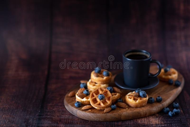 Homemade belgian waffles, white ceramic cup of coffee, milk, teaspoon and coffee beans. Dark rustic background. Space for text in stock images