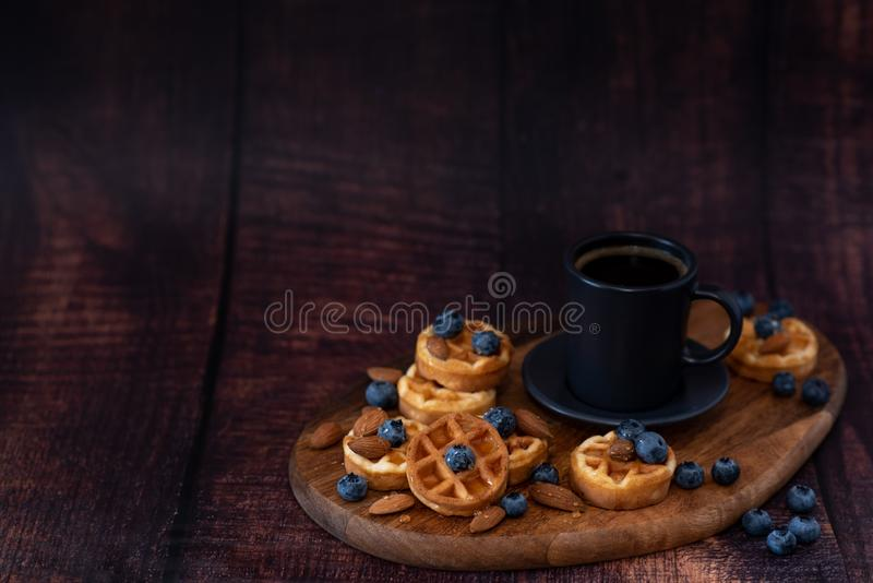 Homemade belgian waffles, white ceramic cup of coffee, milk, teaspoon and coffee beans. Dark rustic background. Space for text in royalty free stock photos