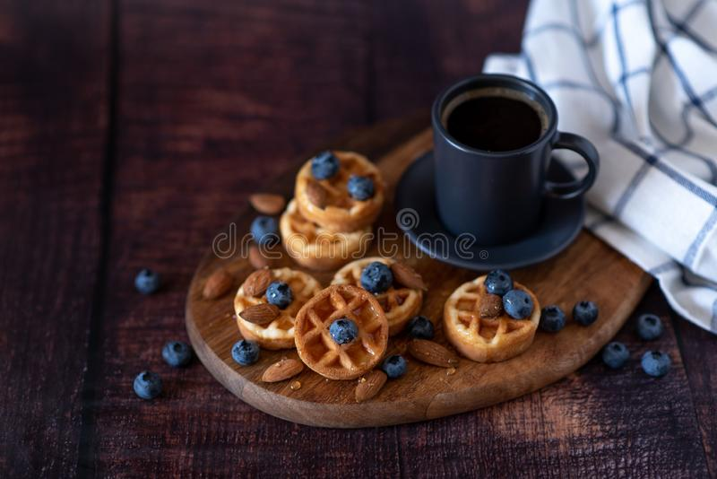 Homemade belgian waffles, white ceramic cup of coffee, milk, teaspoon and coffee beans. Dark rustic background. Space for text in royalty free stock image