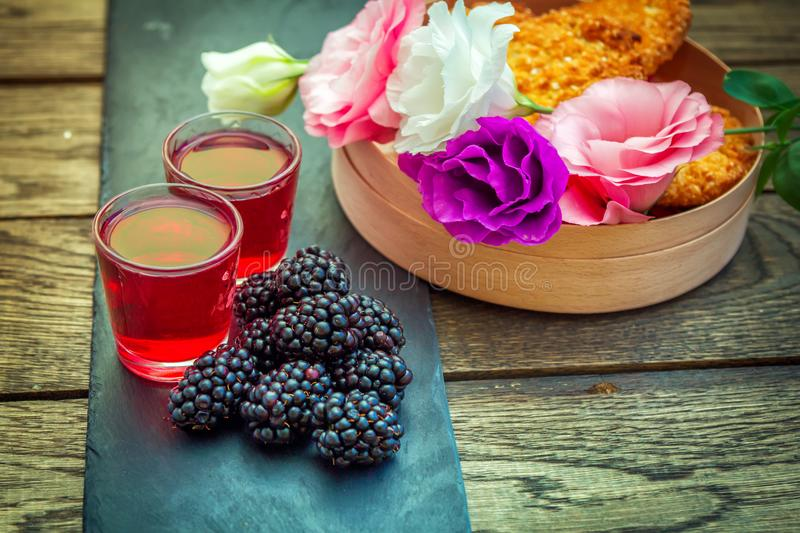 Homemade berry liqueur with fresh ripe blackberries stock image