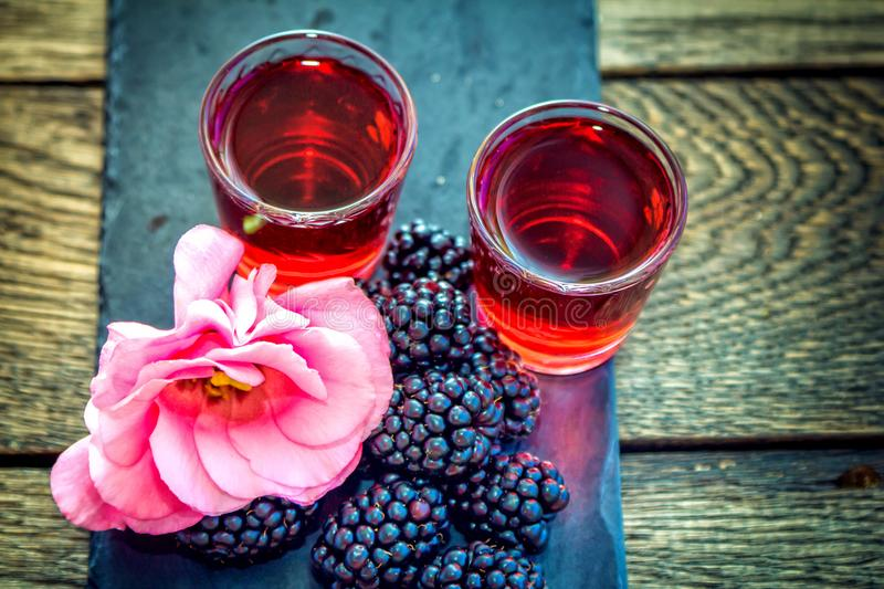 Homemade berry liqueur with fresh ripe blackberries royalty free stock photos